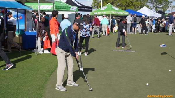 Golfers demo putting gear on the putting green